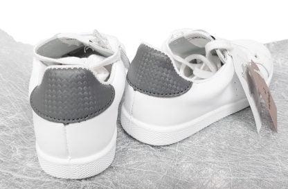 une basket tige basse en cuir blanc et col gris signée victoria, modèle à lacets et 1 zip