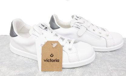 une basket tige basse en cuir blanc et col anthracite fermée par 1 lacet et 1 zip, modèle victoria