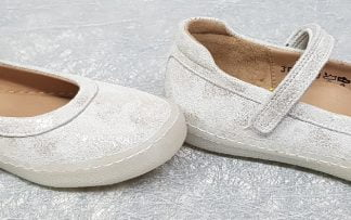 une ballerine pour enfant, la New School Baby de Pom d'Api, elle est en cuir blanc avec des nuances platines et fermée par 1 bride à velcro sur le coup de pied