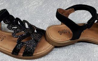 un style salomé avec sa large lanière découpée et imprimée argent sur le pied pour le nu-pied Ion de Bellamy pour fille, ces chaussures pour enfants sont en cuir velours noir et fermé par 1 bride à velcro