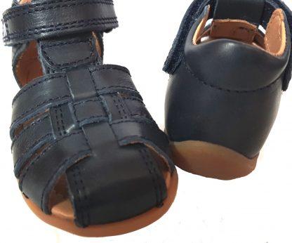 un cuir marine pour le nu-pied enfant Bisgaard, un modèle doté d'un contrefort pour les premiers pas de bébé avec velcro