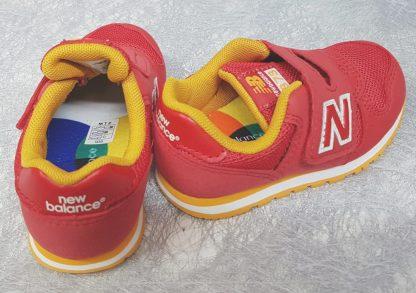 une basket enfant en textile rouge et empiècements jaunes pour le modèle New balance pour garçon IV373 avec 1 velcro