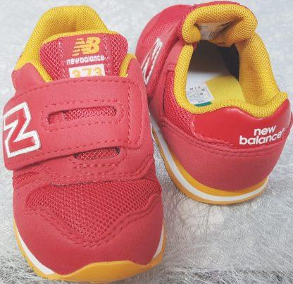 un textile rouge et empiècements jaune pour la basket garçon fermée par 1 velcro, chaussure enfant New Balance