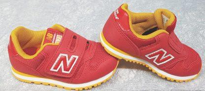 une basket baszse garçon en textile rouge et empiècements jaunes, chaussure enfant New Balance fermée par 1 velcro, modèle IV373