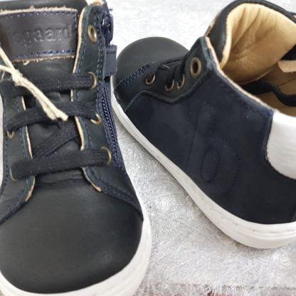 un cuir noir et son col matelassé gris clair sur une semelle gomme blanche pour la basket enfant de Bisgaard, ce modèle est fermé par 1 lacet et 1 zip