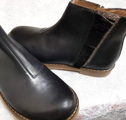 une boots pour enfant signée Pom d'Api. Trip Fringe est en cuir noir joliment décoré d'une bande glitter recouverte de franges noir irisées sur la tige, modèle fermé par 1 zip