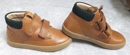 une chaussure mi-montante fermé par 2 velcros, modèle Play Desert en cuir camel et col lainé vert foncé de Shoo Pom