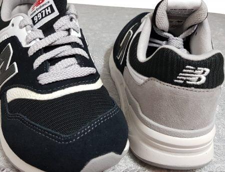 la basket pour garçon de New balance est doté d'un lacet, elle est en cuir et textile blanche, noire et grisde, modèle enfant GR997
