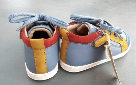 La Bouba Bi Zip est un bottillon pour premiers pas en cuir lisse bleu et ocre avec un col matelassé velours rouge, modèle Shoo Pom fermé par 1 lacet et 2 zips