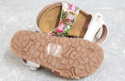une sandale enfant Stones and Bones en cuir blanc et doté d'une lanière à boucle imprimé fleurs, modèle Crast fermé par 1 brider à velcro et doté d'une semelle anatomique