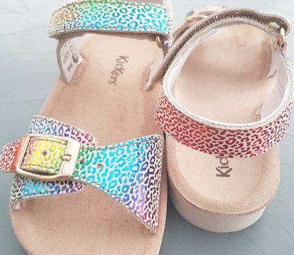 une sandale pour fille avec une semelle anatomique, une bride à velcro et une lanière à boucle sur l'avant du pied. Odyssa en cuir métal imprimé multicolore signée Kickers