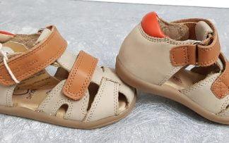 un cuir nubuck beige avec son col matelassé en cuir orange pour la Pika Scratch de Shoo Pom, un nu-pied fermé pour premiers pas . Un modèle doté de 2 velcros en cuir camel.
