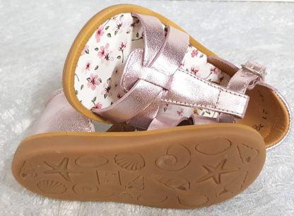 un nu-pied pour premiers pas en cuir métallisé rose (blush) et une semelle intérieure cuir fleuri, modèle doté d'un contrefort et d'une bride à boucle, Poppy Xexe de Pom d'Api