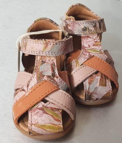 Cheri de Bisgaard, un joli nu-pied à bout protégé et contrefort pour enfant en cuir effet python rose imprimé fleurs. Cette sandale est dotée de brides cuir rose, vernis saumon et imprimé fleurs, elle est fermée par 1 bride à velcro