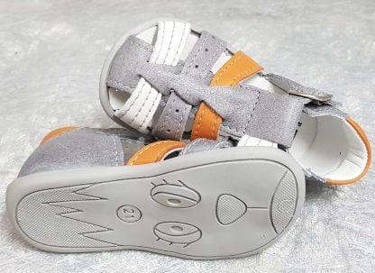 Un nu-pied fermé pour premiers pas en cuir gris clair et lanières cuir blanc et orange. Ce modèle est doté d'un contrefort et fermé par 1 bride à boucle
