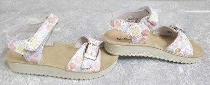 une sandale pour fille avec sa semelle anatomique et sa bride à velcro. Ce modèle en cuir blanc imprimé est doté d'une lanière à boucle sur l'avant et d'une semelle extérieure crantée très souple