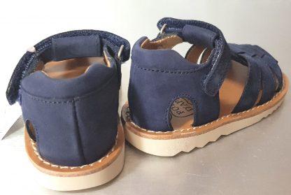 nu-pied avec contrefort pour premiers pas en nubuck marine la Waff Papy. Une sandale Pom d'Api dotée de multiples lanières sur le pied et fermée par 1 bride à velcro