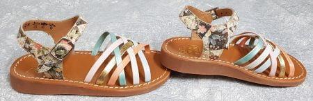 une mixité de cuir platine imprimé et vernis pastel pour le jeu de lanières entrecroisées sur l'avant du pied pour le nu-pied enfant Yapo Lux Bella de Pom d'Api. Une sandale fermé par 1 bride à boucle