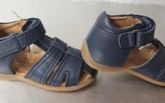 un cuir marine pour le nu-pied premiers pas Abel avec contrefort et col matelassé. Une sandale à bout protégé et fermée par 1 velcro signée Bisgaard