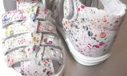 Dora, une sandale enfant en cuir blanc imprimé multicolore avec contrefort. Un modèle Bellamy fermé par 1 bride à velcro