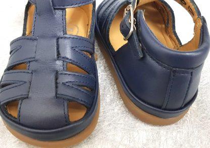 New Flex, un nu-pied en cuir lisse marine doté d'un contrefort avec col matelassé, de multiples lanières, bout protégé et fermé par 1 bride à boucle. Une chaussure premiers pas de Pom d'Api