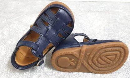 une chaussure enfant Pom d'Api, modèle Neww Flex en cuir marine et contrefort fermé par 1 bride à boucle
