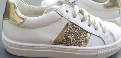 Chaussure enfant Nörvik en cuir lisse blanc et empiècements cuir métal et glitter or. Basket tige basse Sol fermée par 1 lacet et 1 zip