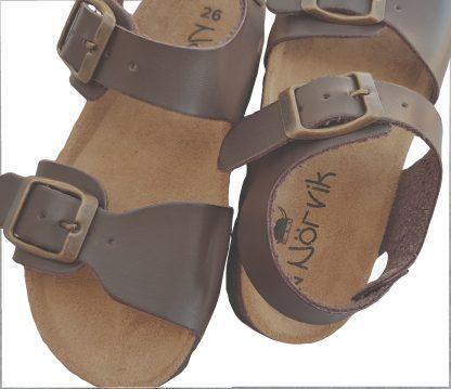 Un cuir marron pour la sandale gaçon Zap dotée d'une semelle anatomique. Ce nu-pied signé Nörvik se ferme par 1 bride à boucle et une lanière à boucle a été rajouté sur l'avant du pied.
