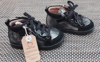La Bouba Bi Zip pour premiers pas est une chaussure enfant Shoo Pom en cuir velours noir et argent avec un cuir vernis noir. Ce modèle est fermé par 1 lacet et 2 zips.
