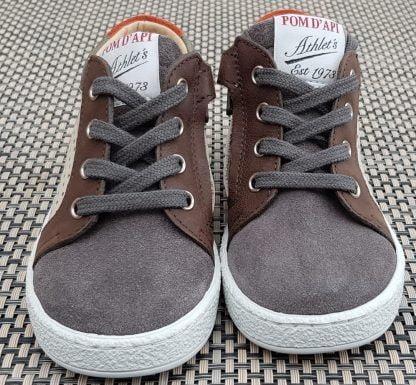 Une chaussure Pom d'Api pour premiers pas, la Mousse Zip Clay à lacets et 1 zip, modèle en cuir beige et cuir velours gris et kaki.