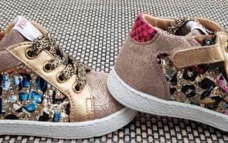 Pour les premiers pas, une sneaker en cuir velours rose irisé et cuir lisse métal or doté d'un col matelassé rose et noir avec un imprimé multi et glitter or sur le côté. Cette chaussure enfant est fermée par 1 lacet et 1 zip, modèle Mousse Zip Top de Pom d'Api Pom d'Api