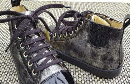 une mixité de cuir velours noir et argent et un cuir vernis noir pour la basket haute Play Jodlace de Shoo Pom, cette sneaker enfant est fermèe par 1 lacet et 1 zip