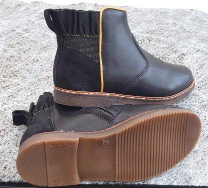 Classique et élégante un brin fantaisie la boots City Frizz est vêtue d'un cuir lisse noire et dotée d'un élastique noir irisé or et gansé or, modèle Pom d'Api fermé par 1 zip