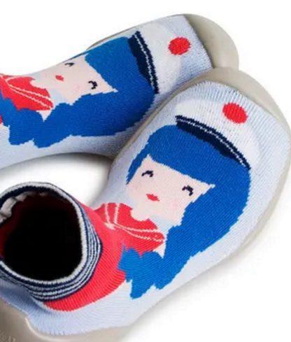 Une casquette de marin blanche et noire sur un visage de pin up bleu et rose sur un fond bleu ciel, c'est le chausson en laine Pin Up de Collégien? Ce modèle s'enfile comme une chaussette, il est doté d'une semelle caoutchouc