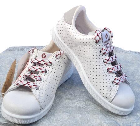 une mixité de cuir lisse et perforé blanc pour la basket enfant Victoria dotée de motifs rouge et fermée par 1 lacet