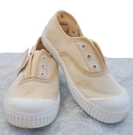 une toile beige et filaments or pour la basket toile enfant signé Victoria dotée d'un élastique sur le pied