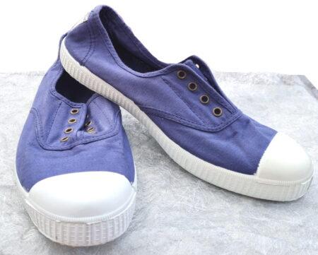 une toile bleue pour la basket avec élastique sur le pied et semelle caoutchouc blanche. Un modèle pour junior signé Victoria