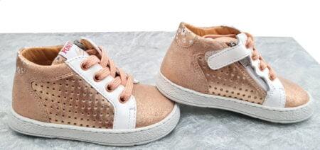 Pour les premiers pas, une sneaker en cuir métal cuivre, cuir lisse blanc et cuir velours irisé cuivre fermée par 1 lacet et 1 zip, modèle Mousse Zip Clay signé Pom d'Api