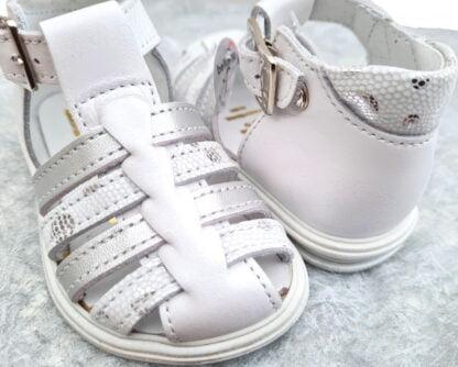 Pour les premiers pas, Playa, un nu-pied cuir blanc nacré et lanières cuir argent et blanc effet python imprimé argent. Une sandale fermée par 1 bride à boucle signée Bellamy