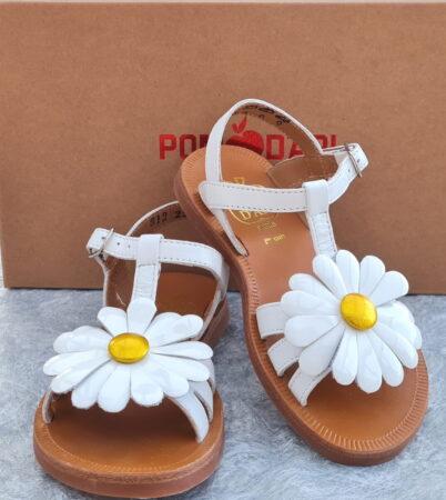 Nu-pied fille Pom d'Api à boucle. Une sandale en cuir blanc jolimlent décoré d'une marguerite en cuir vernis blanc et coeur métal jaune sur les lanières. Chaussure pour enfant de l'été 2021.