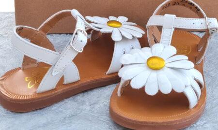 Nu-pied en cuir blanc, joliment décoré sur les lanières avant d'une marguerite en cuir vernis blanc et coeur métal jaune pour la Plagette Big Flo pour fille. Modèle signé Pom d'Api fermé par 1 bride à boucle