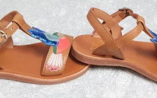 un joli colibri en cuir lisse rose et mètal multicolore orne ce nu-pied pour enfant en cuir lisse camel, modéle Plagette Colibri de Pom d'Api fermè par 1 bride à boucle