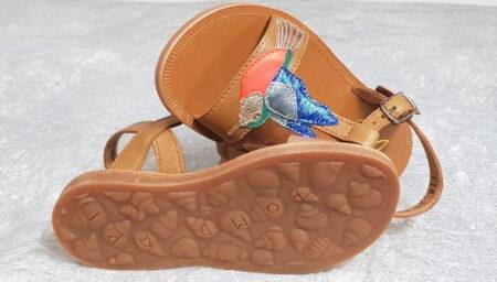 un cuir lisse camel pour le nu-pied enfant Plagette Colibri joliment dècorè d'un colibri sur le pied en cuir lisse et mètal et de feuilles sur le côtè. Une sandale Pom d'Api fermèe par 1 bride à boucle