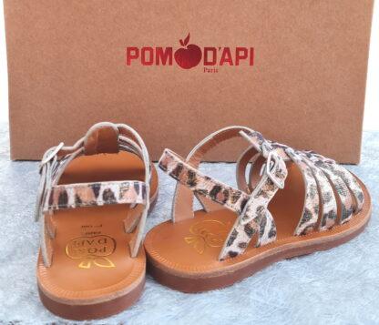 un cuir blanc et platine imprimé léopard pour le nu-pied fille Plagette Strap de Pom d'Api. Ces multiples lanières sur le pied assurent un ajustement parfait et la bride à boucle maintient la cheville.