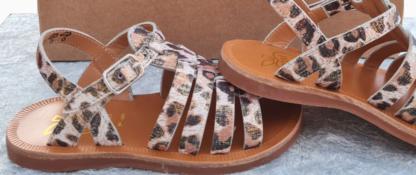 Nu-pied fille Plagette Strap doté de multiples lanières en cuir blanc, platine et imprimé léopard. Une sandale Pom d'Api fermée par 1 bride à boucle