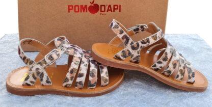 Plagette Strap, un nu-pied pour fille en cuir blanc et platine imprimé léopard. Une sandale doté de multiples lanières sur le pied et fermé par 1 bride à boucle