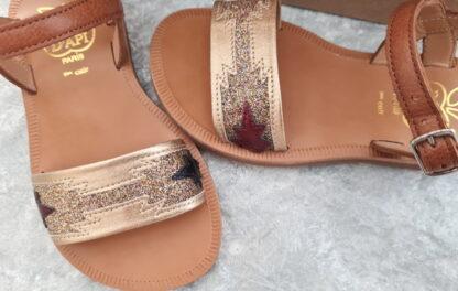 Plagette Zia, un cuir camel rehaussé d'une jolie lanière en cuir métal et glitter platine. Une sandale enfant de Pom d'Api fermée par une bride à boucle