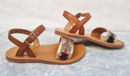 Une sandale fillette et junior en cuir camel et lanière platine joliment décoré de glitter platine et d'une feuille bordeaux et 1 marine. Plagette Zia de Pom d'Api fermée par 1 bride à boucle