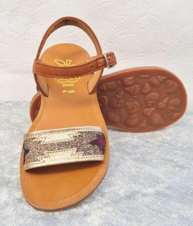 Nu-pied enfant en cuir camel joilment doté d'une lanière métal platine et glitter platine avec 1 feuille bordeaux et 1 marine. Plagette Zia de Pom d'Api fermé par 1 bride à boucle