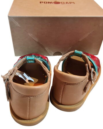Une sandale pour bébé fille en cuir lisse camel et l'avant du pied est une fraise en cuir métal vert et rouge. Poppy Berry est un nu-pied enfant de Pom d'Api fermé par 1 bride à boucle